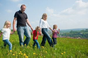 Family walking through grass and flowers