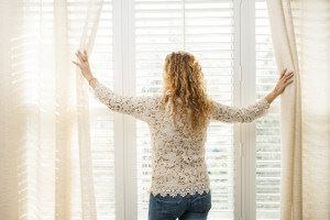 Woman opening window shutters