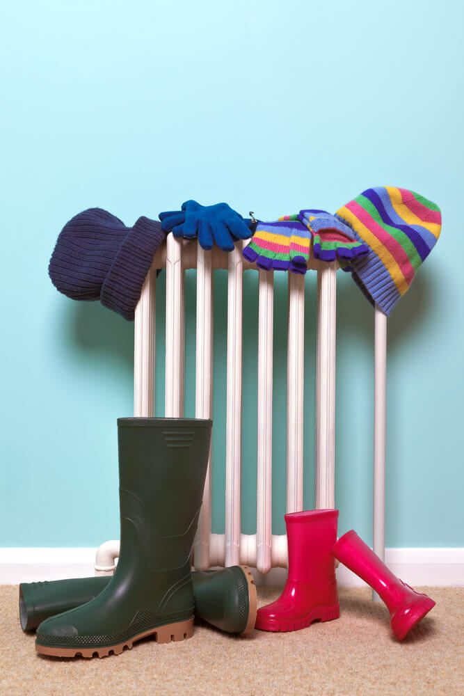 hats and wellies drying by a radiator