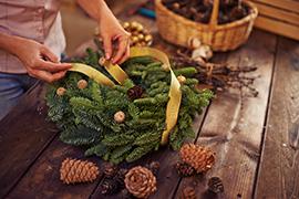 woman making a natural garland wreath