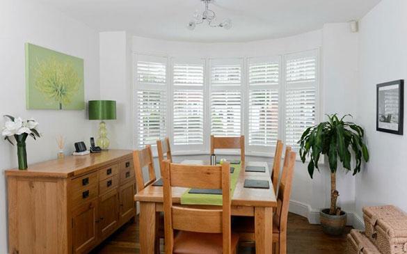 bay window shutter installation in dining room